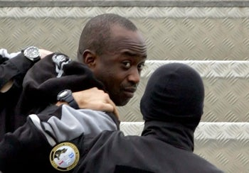 This file photo taken on March 4, 2006 at Abidjan airport shows French alleged gang leader Youssouf Fofana escorted by two plainclothes policemen on the gangway of a Paris-bound plane.