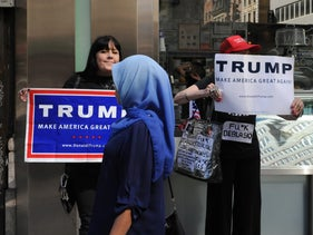 A woman wearing a Muslim headscarf walks past people holding U.S. Republican presidential nominee Donald Trump signs in New York City, September 25, 2016.