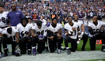 Baltimore Ravens players kneel down during the playing of the U.S. national anthem before an NFL football game against the Jacksonville Jaguars at Wembley Stadium in London, Sunday Sept. 24, 2017
