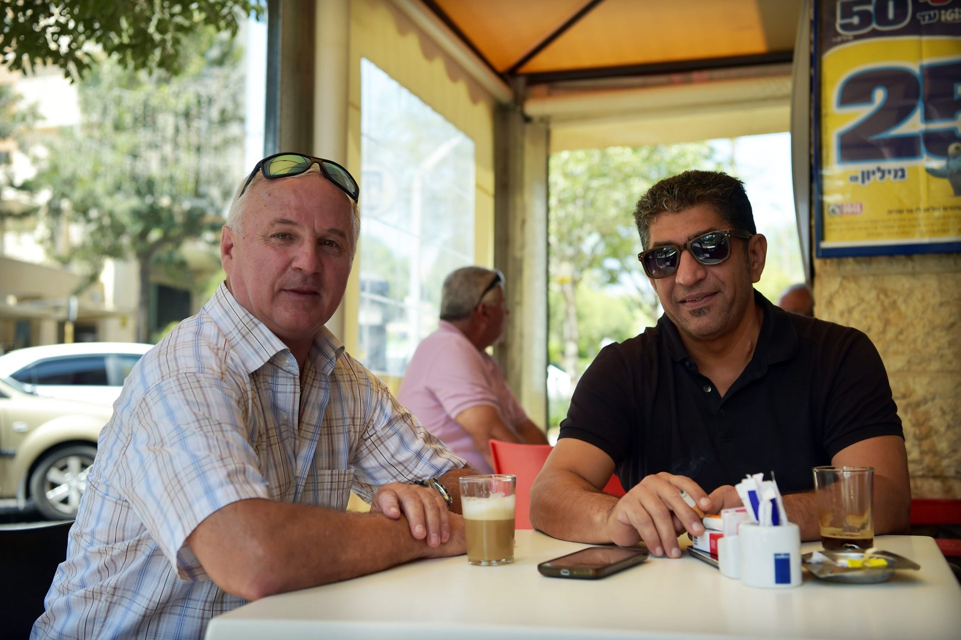 Albert, right, and a friend drinking coffee at a kiosk in Carmiel, northern Israel