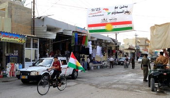 A boy rides a bicycle with the flag of Kurdistan in Tuz Khurmato, Iraq underneath a sign supporting the upcoming Kurdish independence referendum on September 24, 2017.