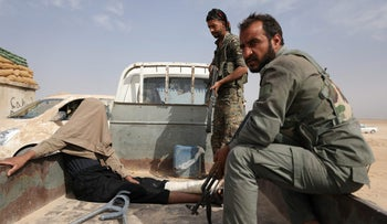 Fighters from the Syrian Democratic Forces after arresting a wounded man during their fighting with Islamic State in Deir al-Zor, Syria, September 24, 2017.