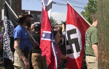 Demonstrators carrying Confederate and Nazi flags during the Unite the Right rally in Charlottesville, Virginia, August 12, 2017.