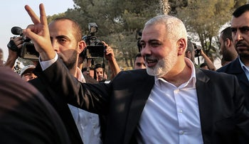 Hamas Chief Ismail Haniyeh flashes the victory gesture upon his arrival on the Palestinian side of the Rafah border crossing, in the southern Gaza Strip on September 19, 2017. / AFP PHOTO / SAID KHATIB