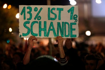 """A demonstrator's placard reads: """"13 percent is a disgrace"""", referring to the electoral gains made by the far-right anti-immigration Alternative fuer Deutschland (AfD) party. Berlin, September 24, 2017"""