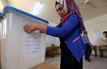 An employees from the Independent High Electoral Referendum Commission prepares the voting station ahead of the referendum for the Kurdistan region, in Arbil, September 24, 2017.