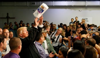 U.S. President Donald Trump tosses rolls of paper towels to people at a hurricane relief distribution center at Calvary Chapel in San Juan, Puerto Rico, October 3, 2017.
