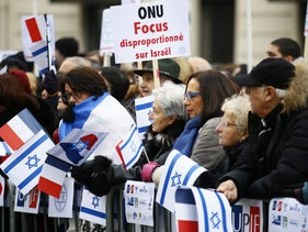 """Pro-Israel demonstrators hold a placard reading """"United Nations Organization Disproportionate Focus on Israel"""" during a gathering in front of the Israeli Embassy in Paris, January 15, 2017."""