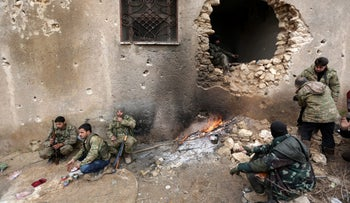 Rebel fighters rest near a hole in the wall on the outskirts of al-Bab in northern Syria, January 15, 2017.