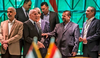 Fatah's Azzam al-Ahmad speaks with Hamas' Saleh al-Aruri after signing a reconciliation deal in Cairo, Egypt, October 12, 2017.