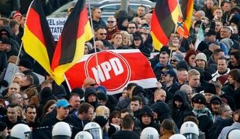 File photo: Demonstrators hold a banner with the logo of the far-right National Democratic Party in Cologne, Germany, January 9, 2016.