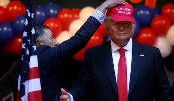 A worker puts a hat on of a life-sized wax statue of U.S. President-elect Trump at Madrid's wax museum, January 17, 2017.