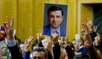 A supporter holds a portrait of the detained leader of Turkey's pro-Kurdish Peoples' Democratic Party (HDP) Selahattin Demirtas at the parliament in Ankara, November 8, 2016.