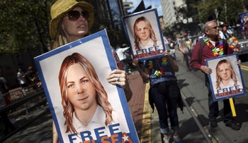 People hold signs calling for the release of imprisoned WikiLeaks whistleblower Chelsea Manning in San Francisco.