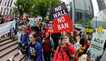 Protesters wave signs and chant during a demonstration against U.S. President Donald Trump's revised travel ban outside a federal courthouse in Seattle, May 15, 2017.