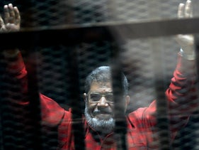 Ex-Egyptian President Mohammed Morsi raises his hands inside a defendants cage in a makeshift courtroom in Cairo.