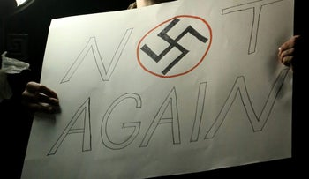 A man holds a sign with a swastika displayed during a protest against U.S. President-elect Donald Trump in New York on November 18, 2016.