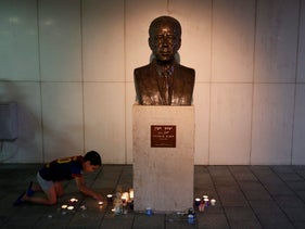 A boy lights a memorial candle next to a bust of Yitzhak Rabin during a memorial event in his honor in Tel Aviv, November 5, 2016.
