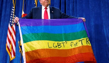 "Then-Republican presidential nominee Donald Trump holds up a rainbow flag with ""LGBT's for TRUMP"" written on it at a campaign rally in Colorado, on Oct. 30, 2016."