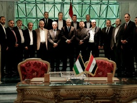 Fatah and Hamas officials pose for a photograph after a reconciliation deal is signed in Cairo, Egypt, Thursday, October 12, 2017