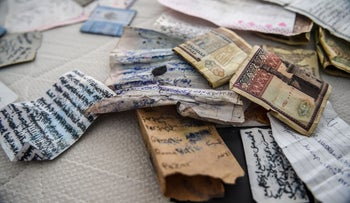 A picture taken on January 17, 2017 shows pieces of paper and money in the apartment where the main suspect in the Reina nightclub rampage was arrested by Turkish police the night before, in Istanbul.