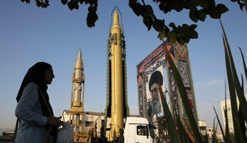 In this September 25, 2016 file photo, Iranians walk past a Ghadr-F missile displayed at a Revolutionary Guard hardware exhibition at Baharestan Sq. in downtown Tehran, Iran.