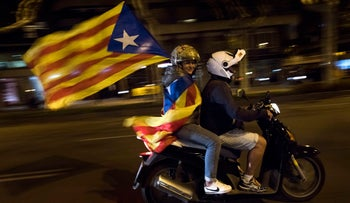 A woman holds an estelada or independence flag on a motorcycle after taking part on a protest against the National Court's decision to imprison civil society leaders without bail, in Barcelona, Spain, Tuesday, Oct. 17, 2017. Protesters were gathering for a fresh round of demonstrations in Barcelona Tuesday to demand the release of two leaders of Catalonia's pro-independence movement who were jailed in a sedition probe.