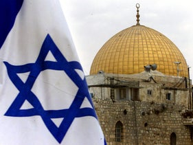 The Israeli flag flies in front of the golden roof of the Dome of the Rock in Jerusalem's Old City.
