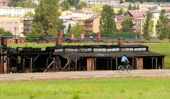 A cyclist ride next to burnt barracks of former Nazi death camp Majdanek in Lublin August 10, 2010.