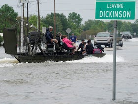 People are rescued by airboat as they evacuate flood waters from Hurricane Harvey in Dickinson, Texas August 27, 2017.
