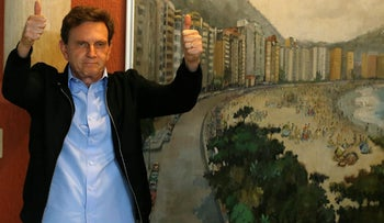 Senator Marcelo Crivella, candidate for Rio de Janeiro mayor, gestures to photographers after voting during the municipal elections at a polling station in Rio de Janeiro, Brazil, October 30, 2016.