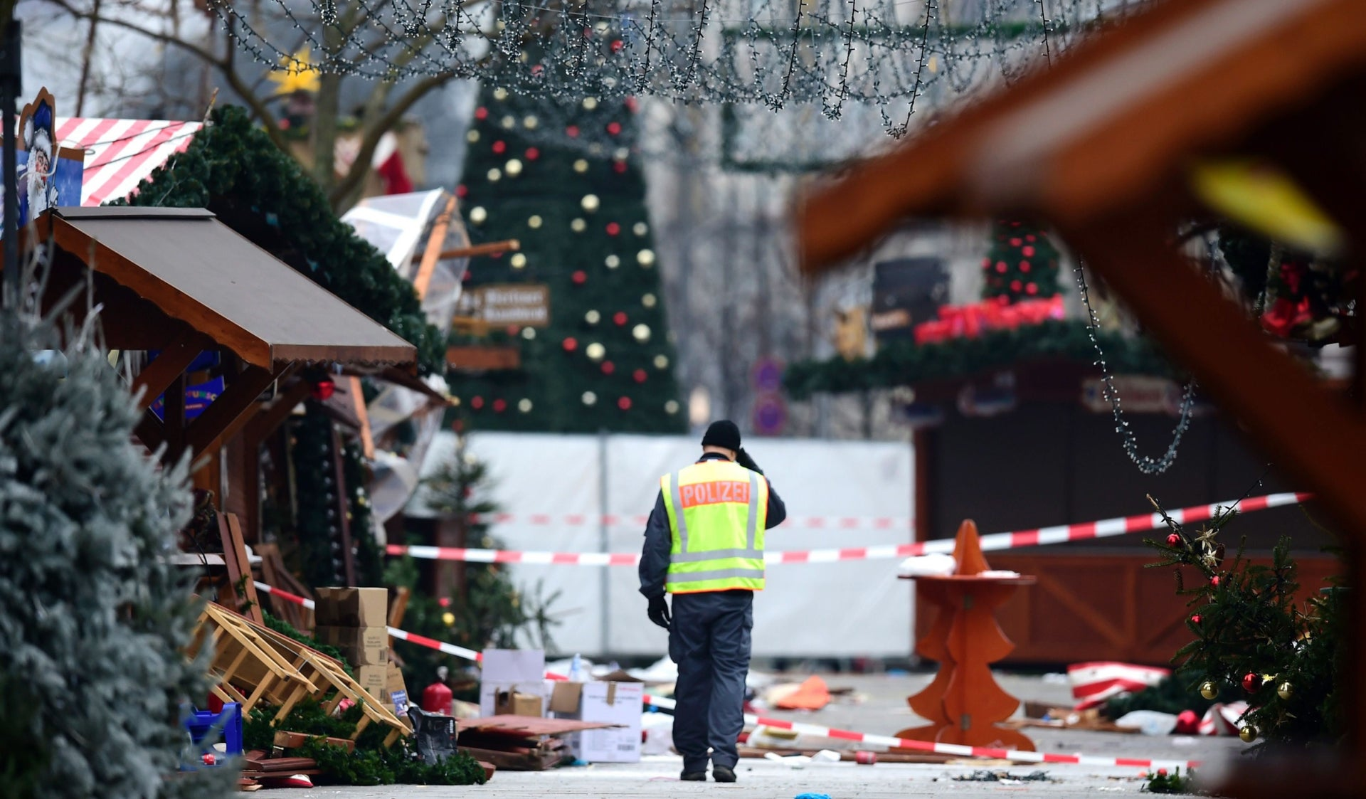 A policeman walks at the Christmas market near the Kaiser-Wilhelm-Gedaechtniskirche (Kaiser Wilhelm Memorial Church), the day after a terror attack, in central Berlin, on December 20, 2016.
