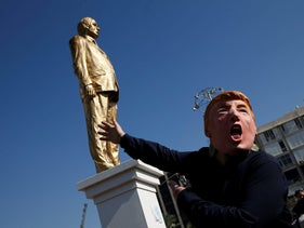 A person wearing a Donald Trump mask, gestures near a statue of Israeli Prime Minister Benjamin Netanyahu, by Israeli sculptor Itay Zalait, at a square outside Tel Aviv's city hall, December 6, 2016.