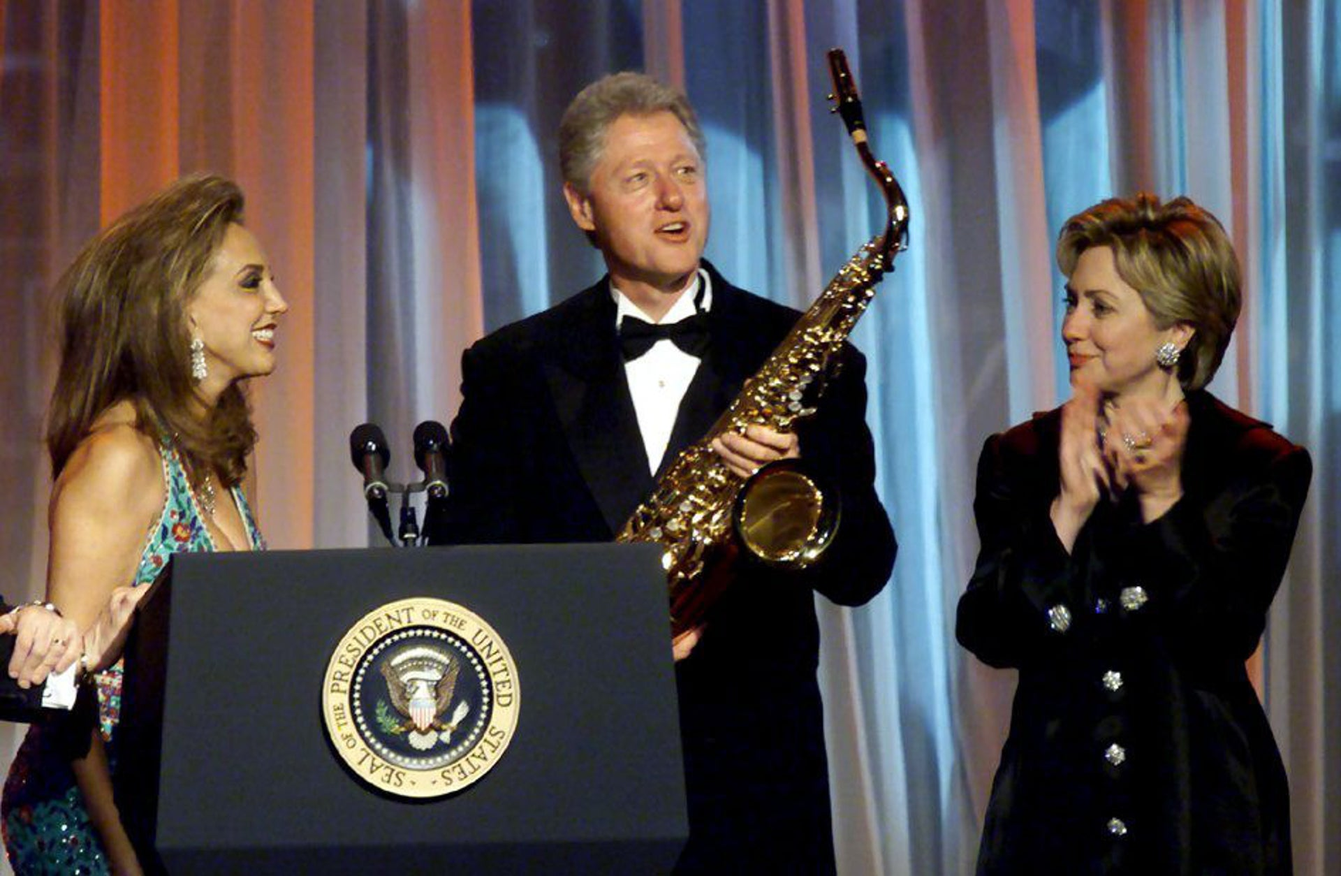 Denise Rich (L) presents former U.S. President Bill Clinton with a saxaphone at the G&P Foundation gala in New York City, in this file photo from November 30, 2000. Former President Clinton has come under intense scrutiny since he left office following a January 20 pardon he granted Denise Rich's ex-husband, financial trader Marc Rich just hours before leaving the White House. The pardon has resulted in questions in Congress and elsewhere over whether the pardon was related to contributions and pledges by Ms. Rich to the Democratic party and the Clinton Library project. First lady Hillary Rodham Clinton applauds at right.