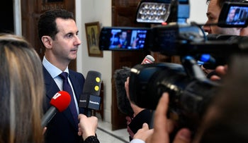Syrian President Bashar Assad, left, speaks with French journalists in Damascus, Syria, Jan. 9, 2017.