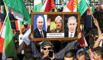 An Iraqi Kurd raises frame of Putin, Netanyahu, and Iraqi Kurdistan President Massud Barzani during a demonstration outside the UN Office in Erbil, on October 21, 2017