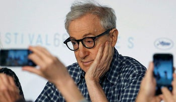 Journalists take pictures with their mobile phones as director Woody Allen attends a news conference during the 68th Cannes Film Festival in Cannes, southern France, in this May 15, 2015 file photo