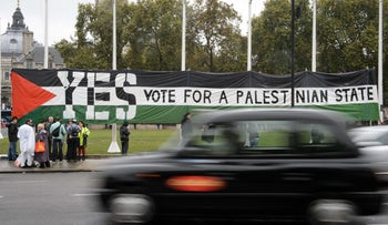 Pro-Palestinian supporters position a giant banner calling for a recognized Palestinian state, Parliament Square, central London, October 13, 2014.