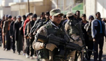 An Iraqi soldier passes scores of Iraqi male residents rounded up in hopes of offering information on any Islamic State members among them, in the Gogjali neighborhood, in Mosul, Iraq, Thursday, Nov. 24, 2016.