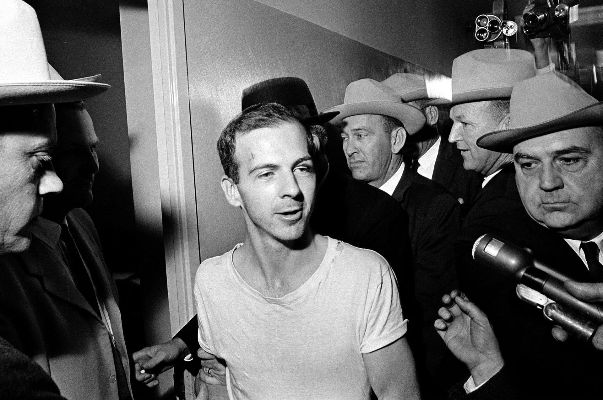 FILE - In this Nov. 23, 1963, file photo, surrounded by detectives, Lee Harvey Oswald talks to the media as he is led down a corridor of the Dallas police station for another round of questioning in connection with the assassination of U.S. President John F. Kennedy. President Donald Trump is caught in a push-pull on new details of Kennedyג€™s assassination, jammed between students of the killing who want every scrap of information and intelligence agencies that are said to be counseling restraint.  How that plays out should be known on Oct. 26, 2017, when long-secret files are expected to be released. (AP Photo)
