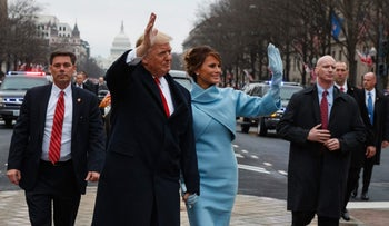 President Donald Trump waves as he walks with first lady Melania Trump during the inauguration parade in Washington, DC, on January 20, 2107.