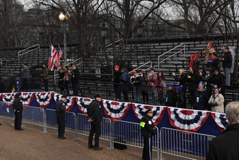Supporters of U.S. President Donald Trump and First Lady Melania Trump watch as they drive the inaugural parade route on Pennsylvania Avenue in Washington, DC, on January 20, 2017.