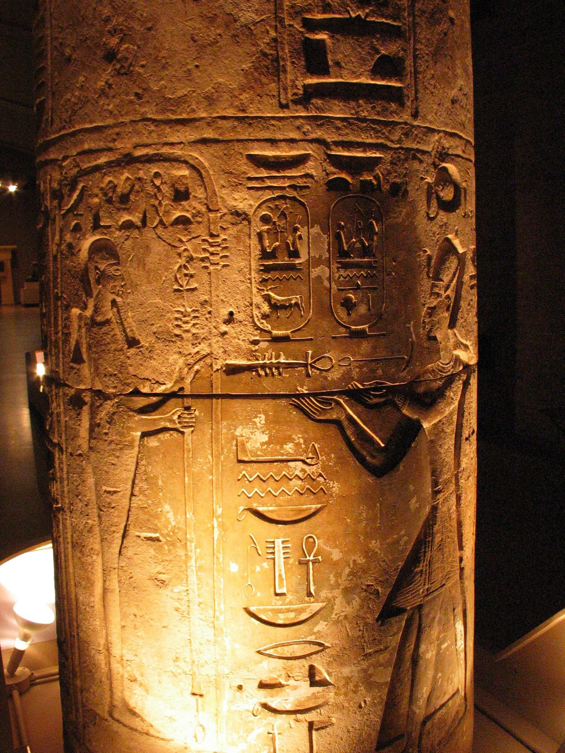 Merenptah makes an offering to the god Ptah on this stone column. From the Museum of Archaeology and Anthropology at the University of Pennsylvania, Philadelphia. The picture shows light shining on very well preserved images and hieroglyphics carved onto a stone column.