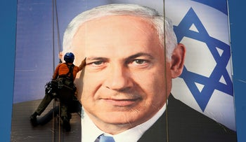 A worker installing a banner depicting Prime Minister Benjamin Netanyahu in Tel Aviv during the 2013 election campaign.
