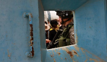 A soldier guards a Purim celebration in Hebron.
