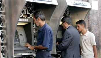FILE PHOTO: Palestinians use automated teller machines (ATMs) of the Bank of Palestine in Gaza September 25, 2007.