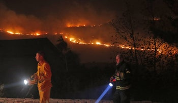 Fires burn in the horizon as firefighters battle to control a fire that broke out in Nataf, west of Abu Ghosh, along the border with the West Bank on November 25, 2016.