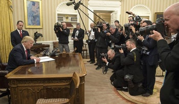 U.S. President Donald Trump signs an executive order commanding federal agencies to try to waive or delay requirements of the Affordable Care Act, January 20, 2017.