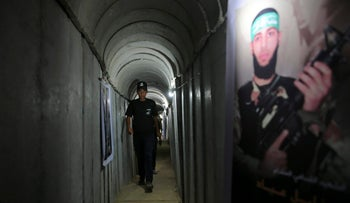 A Palestinian youth walks inside a tunnel used for military exercises during a weapon exhibition at a Hamas-run youth summer camp, in Gaza City, July 20, 2016.