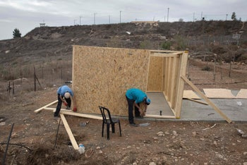 Israeli settler youths build a new wooden structure in the settlement outpost of Amona.